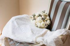 En épousant le bouquet rustique et le blanc habillez sur la chaise barrée par vintage Intérieur nuptiale de pièce Photographie stock libre de droits