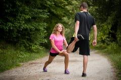 En étirant l'échauffement exercez-vous avant de commencer à courir par des couples Image stock