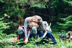 En étreignant le  de Ñ hildren se reposer en clairière de forêt image stock