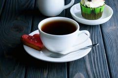 En Ñ- upp av doftande te med den läckra kakan i den vita maträtten arkivbilder