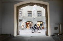 En ögonblicksögonkast från en grå bakgata fångar mannen att rida en cykel mot ljus souvenir shoppar fönster royaltyfria bilder