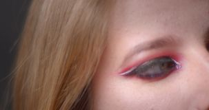 En ögonfors av blond modell med ljusa sminkblinkar in i kamera som fast beslutsamt håller ögonen på på bokehbakgrund stock video