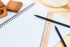 En öppen anteckningsbok och en linjal med två blyertspennor och ett pussel på en träbakgrund arkivbilder