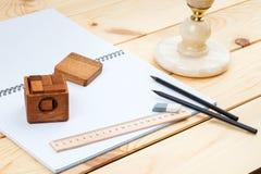 En öppen anteckningsbok och en linjal med två blyertspennor och ett pussel på en träbakgrund royaltyfri fotografi