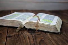 En öppen bibel och ett guld- kors på träbakgrund arkivfoton