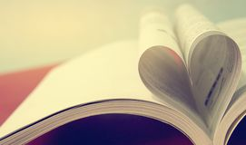 En öppen bok från hjärtaform som förälskelsesymbol Hjärtaform för selektiv fokus från den pappers- boken Förälskelse- och omsorgb royaltyfri foto