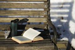 En öppen bok, en glass kopp med ett lock med kaffe och en öppen cho Royaltyfria Foton