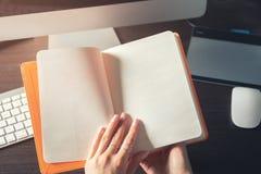 En öppen bok i händerna Arkivbild