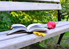 En öppen bok ligger på en bänk i parkera, bredvid den är ett rött äpple och gulinghöstsidor arkivbild