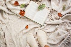En öppen bok ligger på en beige ullpläd Närliggande är stupade sidor för höst från träd och ben med stack vita ullsockor arkivbilder
