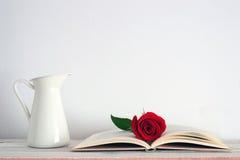 En öppen bok med en röd rosblomma på den arkivfoto