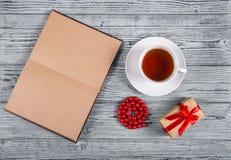 En öppen bok med tomma sidor, en kopp av svart te, en gåva och röda pärlor Top beskådar kopiera avstånd Arkivbilder