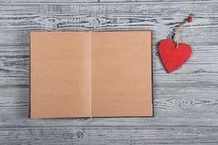 En öppen bok med tomma sidor och en träbokmärke i form av en hjärta Röd trähjärta på en grå bakgrund Arkivfoto