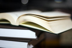 En öppen bok på en bokbunt Royaltyfria Bilder