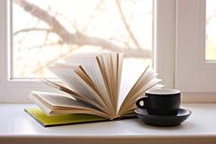 En öppen bok på fönstret och en kaffekopp arkivfoto