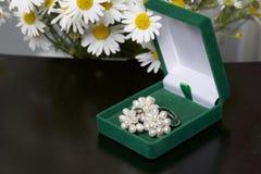 En öppen grön sammetask för smycken I den ligger en uppsättning: en cirkel och örhängen med pärlor Bredvid vasen är en bukett av  Royaltyfria Foton