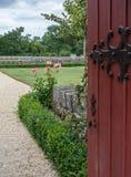 En öppen port inviterar dig till trädgården med rosor fotografering för bildbyråer