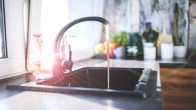En öppen vattenkran i köket stock video