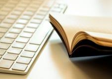 En öppnad bok och ett tangentbord Royaltyfri Foto
