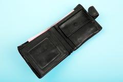 En öppnad lädersvartplånbok med mycket pengar, på ett ljus - blå bakgrund Handväskan med kassa Royaltyfria Foton