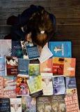En över huvudet sikt av flickaläsning i en bokhandel Arkivbild