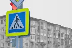 En övergångsställe tecken mot ett grått hus Arkivfoto
