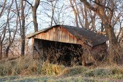En övergiven lantgårdbyggnad på gryningen Arkivfoto