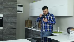 En överviktig grabb att tycka om hans coffe och stirrande på telefonen Den feta mannen ser något som är kuslig eller shoking i in stock video