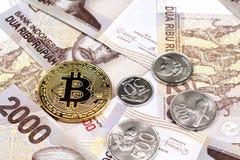 En övre bild för slut av indones 2000 rupiahanmärkningar med guld- bitcoins arkivfoton