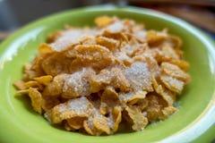 En övre sikt för slut av en bunke av cornflakes med mjölkar och sockrar Royaltyfri Foto