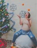 En Año Nuevo la muchacha embarazada cerca del árbol de navidad hace juegos malabares o Foto de archivo