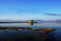En abondonned stonehouse tillsammans med sjön arkivfoton