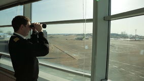 En aeropuerto el controlador aéreo está mirando en distancia usando los prismáticos almacen de metraje de vídeo