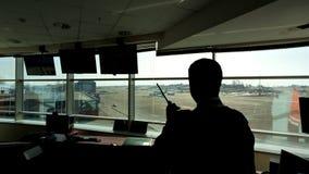 En aeropuerto el controlador aéreo está mirando en la distancia que sostiene la radio almacen de metraje de vídeo