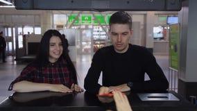 En aeropuerto el par joven se está apresurando para tomar el registro metrajes