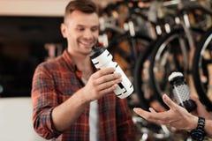 En affärsbiträde på ett cykellager hjälper en ung köpare att välja en vattenflaska för cykelritter arkivfoton