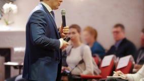 En affärskonferens i korridoren En man som talar på etappen och ger en föreläsning till åhörarna arkivbilder