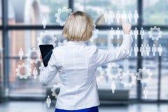 En affärskvinna fungerar med ett digitalt system som består av kugghjul och diagram på pekskärmen på kontorsinre arkivfoto