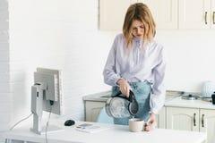 En affärskvinna häller vatten från en kokkärl En i kontoret i vindstilen Arkivbild