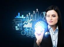 En affärskvinna i formell dräkt är driftig ut beståndsdelen på hologrammet med affärssymboler Royaltyfria Foton