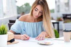 En affärskvinna, i sommar i en kaférestaurang, fyller in ett skriftligt avtal, sätter ett häfte på avtalet som gör royaltyfria bilder