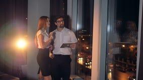 En affärskvinna sammanfogar en affärsman som ser en minnestavlaPC lager videofilmer