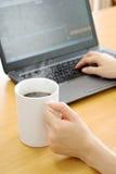 En affärskvinna som använder dennetto boken för minnestavla och dricker kaffe arkivbilder