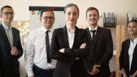 En affärskvinna står i kontoret med hennes armar korsade, hennes anställda står bak henne och leendet, teambuild arkivfilmer