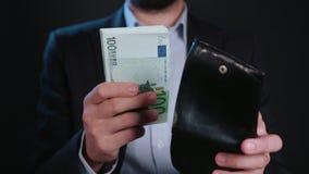En affärsman Hiding Cash i hans plånbok arkivfoto
