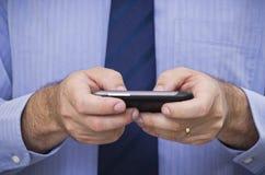 Affärsmannen skrivar meddelandet av pekskärmsmartphonen Arkivfoto