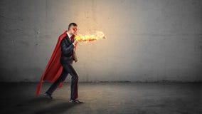 En affärsman i en röd superheroudde och en flammande hand som kastar stansmaskiner på en osynlig fiende på konkret bakgrund Royaltyfria Bilder