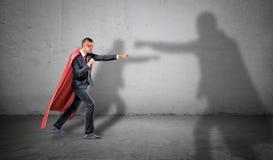 En affärsman i en röd udde och en maskering som av slåss en skugga av en annan större man på konkret bakgrund Arkivfoto