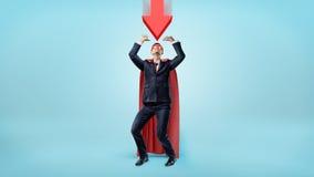 En affärsman i en röd udde och en maskering som kryper ihop under en stor röd pil som ner pekar på honom Royaltyfri Foto