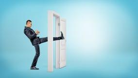 En affärsman i sidosikt sparkar en liten vit dörr som är öppen med hans ben på blåa bakgrunder royaltyfri fotografi